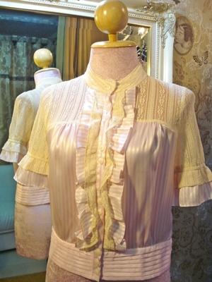 ชาแนล เสื้อคอจีนแขนสั้นผ้าซาตินสีชมพูอ่อนลายทางสีขาว ผ่าหน้าติดกระดุม แต่งระบาย ติดลูกไม้บางสีครีม ชายเสื้อผ้าไหมอัดพลีท /